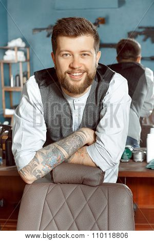 Happy barber leaning on a chair