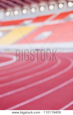 Abstract Blurred Background Of Empty Athletic Racetrack Stadium.