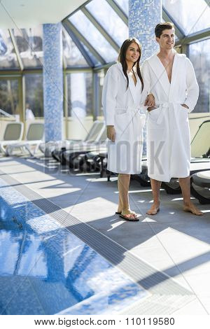 Couple In Love Standing Next To A Pool In A  Robe