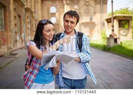 Couple of tourists consulting a city guide searching locations in the street and pointing