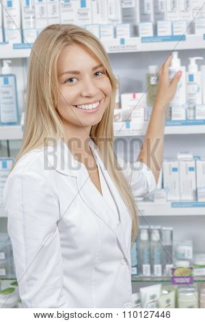 Beautiful pharmacist choosing the product