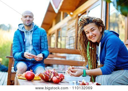 young couple in the garden eating pomegranates