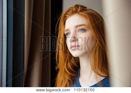 Closeup of young beautiful tender pensive woman with long red hair looking away and dreaming