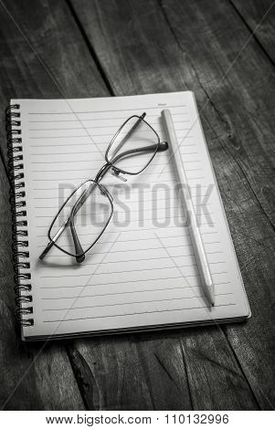 Black And White Photo Of Notebook, Pen And Glasses On The Table