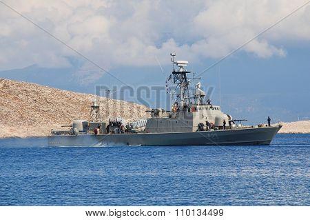 HALKI, GREECE - JUNE 10, 2015: Hellenic Navy Combattante 111N class patrol boat Antipliarchos Mykonios, P23, departs Emborio harbour on the Greek island of Halki. The boat entered service in 1978.