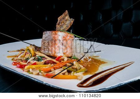 Grilled salmon served with vegetables on white plate