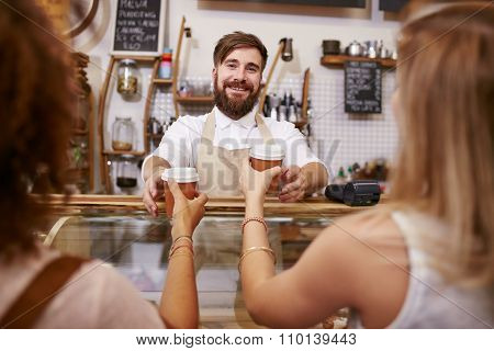 Friendly Man Serving Coffee For Two Women