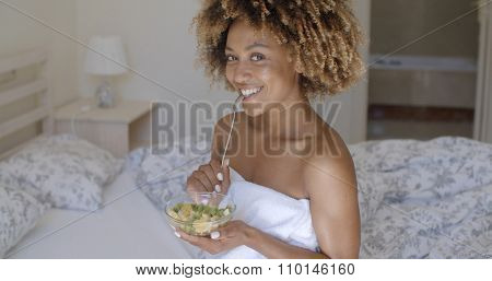 Young african american woman on bed holding vegetable salad and smiling