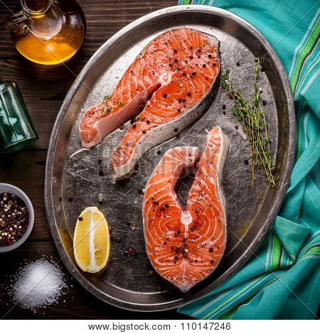 Raw Trout Stakes With Lemon And Rosemary On Metal Tray. Dark Wooden Background.