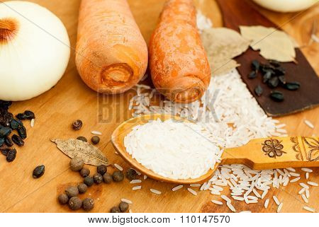 rice in a wooden spoon on the table and spices for pilaf