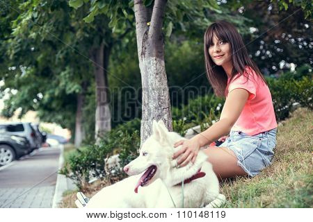 Young girl and her husky dog walking in a city park.