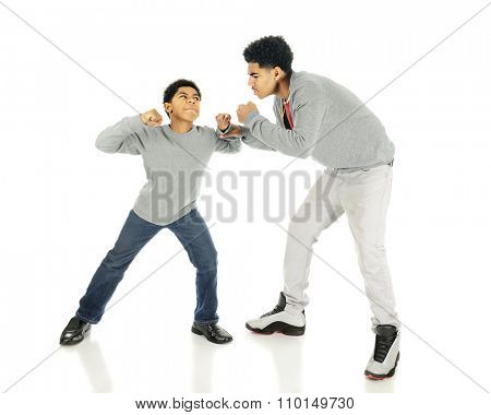 An elementary boy raising his fists towards his much taller older brothers.  On a white background.