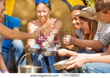 Teen pours soup in metallic plates for her friends