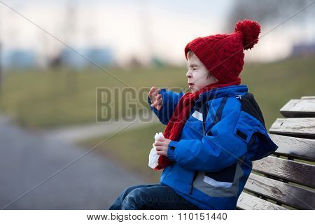 Little Boy, Sneezing And Blowing His Nose Outdoor On A Sunny Winter Day