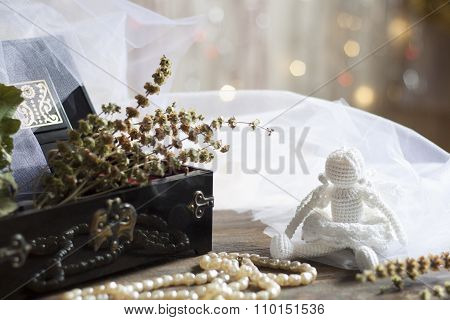 Angel and Pearls necklace in black casket on colorful background bokeh