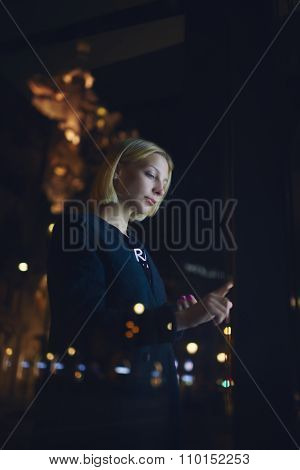 Half length portrait of a young blonde woman standing front big digital screen with information