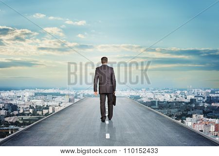 Businessman in suit with suitcase on road and city