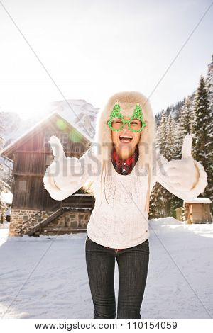 Woman In Christmas Glasses Showing Thumbs Up Near Mountain House
