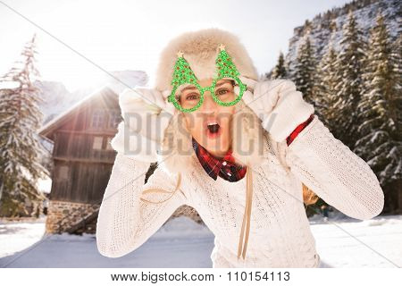 Merry Woman In A Christmas Glasses In Front Of A Mountain House