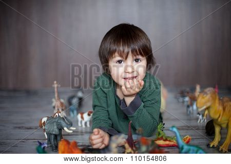 Beautiful Little Boy, Smiling At Camera, Animals And Dinosaurs Around Him