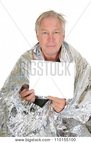 Homeless man wrapped in an emergency survival blanket, holding a piece of paper in front of him with room for your text, isolated on white