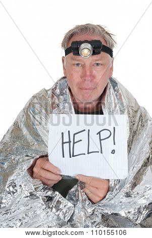 Lost hiker wrapped in an emergency survival blanket, holding a piece of paper in front of him with