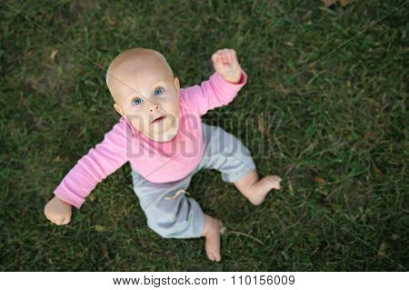 Cute Baby Girl Sitting In Grass Looking At Camera