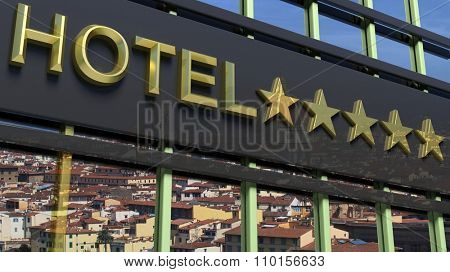 Big metallic glass hotel sign board with five golden stars and city view as background.