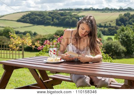 Yound Attractive Woman, Reading A Book Outdoor, Enjoying Coffee And Sweet Scones With Jam