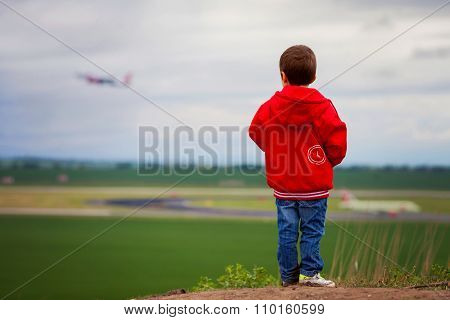 Cute Boy In A Red Jacket, Standing On A Hill, Watching Airplane Taking Off