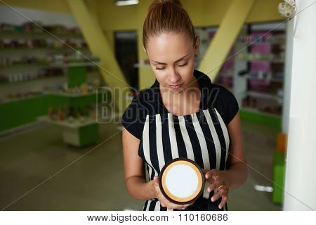 Young charming woman consultant holding plastic jar with copy space for your brand