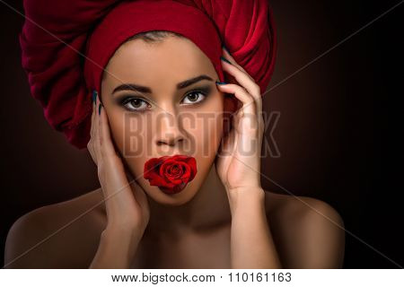 Beautiful girl with red rose in mouth