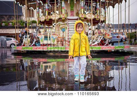 Sweet Child, Boy Watching Carousel In The Rain, Wearing Yellow Raincoat