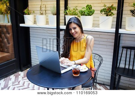 Young Latin female smiling to the camera while sitting front open net-book in coffee shop