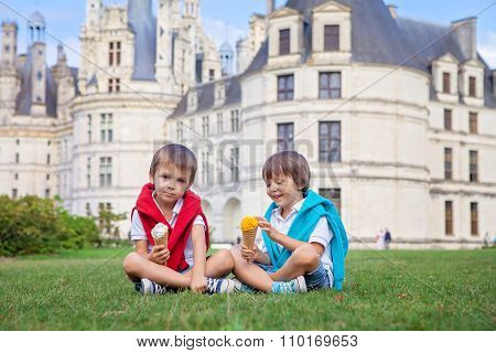 Two Adorable Boys In Casual Clothing, Eating Ice Cream Sitting On A Lawn