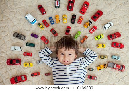 Adorable Boy, Lying On The Ground, Toy Cars Around Him