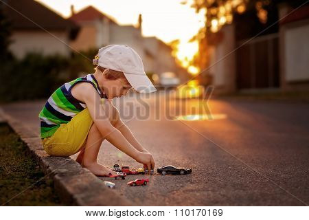 Cute Little Boy, Playing With Little Toy Cars On The Street On Sunset
