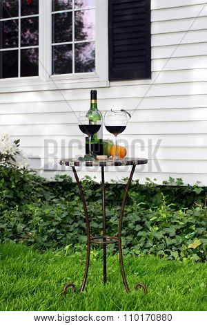 Table With  Bottle Of Wine And Glasses In Garden Near House