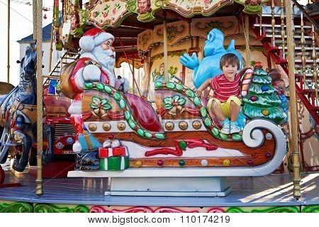Sweet Boy, Riding In A Santa Claus Sledge On A Merry-go-round