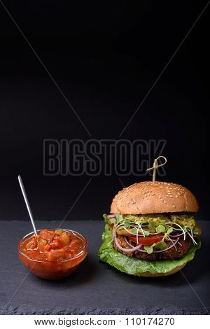 Homemade burger with tomato and zucchini courgette sauce on slate board.