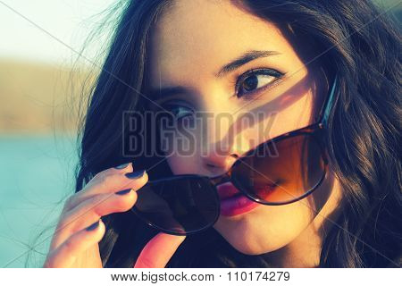 Beautiful Woman Pulling Down Sunglasses While Waching River On Sunny Autumn Day