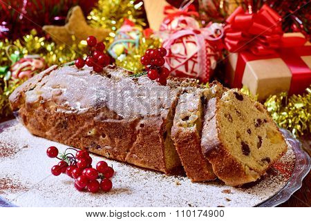 closeup of a fruitcake, on a table full of christmas gifts and ornaments
