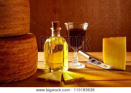 Manchego cheese from Spain with olive oil and red wine on wood