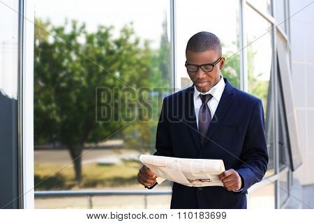 Handsome African American businessman with newspaper near business centre