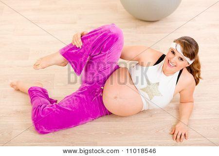Lächelnd schöne schwangere Frauen tun stretching-Übungen