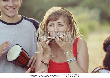 A girl with dreadlocks and harmonica in the forest outdoors