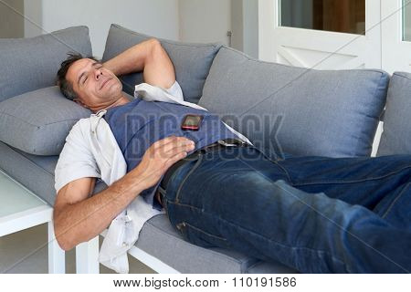 Mature caucasian tired man taking a nap on sofa with cell phone