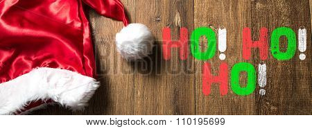 HO! HO! HO! written on wooden with Santa Hat