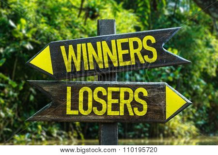 Winners - Losers signpost with forest background
