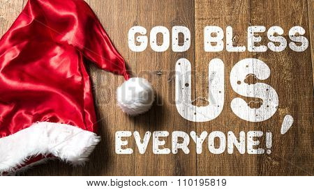 God Bless Us, Everyone! written on wooden with Santa Hat